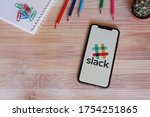 Small photo of Barcelona, Spain - June 11, 2020; Slack Iphone Screen with Colored Pencils on a Bamboo Table. Slack is a cloud-based proprietary instant messaging platform. #Slack