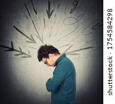 Small photo of Upset introvert person looking down troubled, feels dismayed. Lonely guy experiencing emotional crisis. Man being under pressure at workplace as multiple arrows on the wall pointing to him.