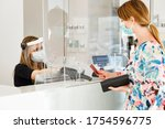Small photo of blonde girl with mask pays at the checkout with a credit card where the cashier is protected by a plexiglass plate and a visor with mask