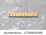 Small photo of regression word written on wood block. regression text on cement table for your desing, concept.