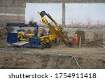Graz/Austria - October 09, 2019: workers on construction site and a heavy duty machinery used for drilling holes in the ground - stock photo