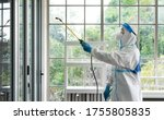 worker from decontamination services wearing personal protective equipment or ppe including suit, face shield and mask. He uses disinfectant to spray and clean scientist lab - stock photo