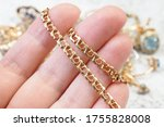 Small photo of gold chain closeup, jewelry scrap of gold and silver and money, pawnshop concept jeweler looking at jewelry through magnifying glass, jewerly inspect and verify