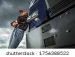 Vintage Semi Truck Driver in Front of His Vehicle. Caucasian Commercial Driver in His 40s. Transportation Industry Theme. - stock photo