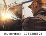 Professional Caucasian Truck Driver in His 40s Getting Into His Truck Cabin. Heavy Duty Transportation Theme. CDL Drive. - stock photo