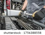 Coach Bus Service Mechanic Choosing Right Tools For the Job. Caucasian Bus Technician and the Tools Set. Transportation Industry Theme. - stock photo