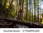 Adventurous Girl Hiking in a Green and Vibrant Rain Forest during a sunny spring day. Taken in Abbotsford, East of Vancouver, British Columbia, Canada. Nature Background Panorama