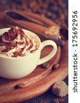 Cup of cappuccino, coffee beans and brown sugar close-up. Toned photo. - stock photo