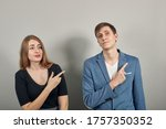 Small photo of Hand pointer with forefinger pointing awry. Index finger to show direction. Means choosing, introducing too. Indicating towards. Young attractive couple boyfriend girlfriend two people