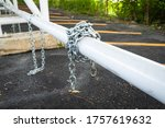 Iron chain curling around a post - stock photo