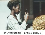 Small photo of Side view of a cute young black woman in eyeglasses taking pics on her smartphone outdoors with rapt attention; a charming focused African girl in a white trench is photographing on cellphone outdoors