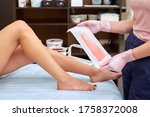 Small photo of The process of female waxing. Beautician Waxing A Woman's Leg Applying Wax Strip. Beautician removes wax with hair from female legs.