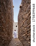Small photo of Dhee Ayn / Saudi Arabia - January 20, 2020: Saudi man wearing white traditional clothes in beautiful stone house village in Dhee Ayn Marble Village