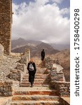 Small photo of Dhee Ayn / Saudi Arabia - January 20, 2020: Two red hair female Western tourists wearing black clothes visiting beautiful stone house village in Dhee Ayn Marble Village in Saudi Arabia