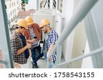 Group of three manual workers drinking coffee, using digital tablet and chatting during break at work, high angle shot - stock photo