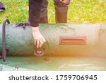 Man outdoors in nature inflating green rubber boat. Preparing for outdoor camping and fishing trip on a summer day - stock photo
