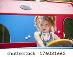 A Girl With Pigtails Driving A...