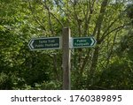 Two Signs Attached To A Wooden...