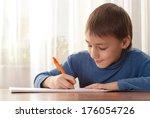 little boy writing a book at