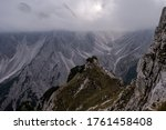 Dolomites Alps. Cadini di Misurina. Italy. Crew of travelers stays on the top of the mountain in heavy fog over a cliff wrapped by white clouds and have relax on background of sharp peaks