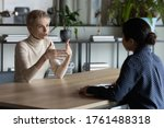 Small photo of Diverse business women sit in front of each other conduct business conversation. Job interview applicant and headhunter talk. Company representative make offer to client convince buy services concept