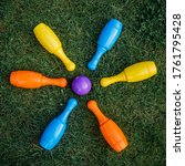 Small photo of Children's set to play bowling on green grass. Ball and colored pins. Kid's game toy. Bowling colorful plastic pins. Active and interesting childhood concept.