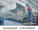 Small photo of Caucasian HVAC Technician Worker in His 40s Testing Newly Installed Warehouse Ventilation System. Commercial Heating, Cooling and Air Ventilation Systems.