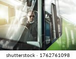 Caucasian Bus Driver Behind the Wheel of Modern Vehicle. Coach Bus Driving Theme. Public Transportation Concept. - stock photo