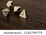 Small photo of Decorative multi-purpose gaming dice. This set of dice of an interesting pattern carved out of each dice in the set. The dice have the highest number on each one replaced with an arcane symbol.