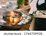 Small photo of The cook roasts the courgettes. Grilled vegetables. Round bowl-shaped grill with a fire inside.