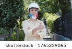 Virus and disease prevention concept. Portrait of an engineer woman wearing a protective medical mask and hard hat with the France flag. Protection against coronavirus and other diseases.