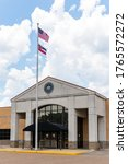 Small photo of Brandon, MS / USA - June 20, 2020: Rankin County Courthouse Annex building with the seal of the board of Supervisor and a Mississippi flag and USA Flag flying above it.
