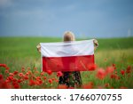 Small photo of Blond girl holding flag of Poland in the poppy field. Back view. Polish Flag Day. Independence Day. Travel and learn polish language concept.