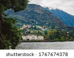 Villa on the shore of lake Como against the backdrop of the majestic Alpine mountains. Quiet and cozy place in the North of Italy. Popular tourist attraction in Lombardy, Northern Italy.  - stock photo
