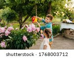 A little boy with his sister watering beautiful pink peony flowers during sunset in the garden and smiling. Agriculture, gardening - stock photo