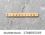 Small photo of Stakeholder word written on wood block. Stakeholder text on cement table for your desing, concept.