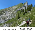 St. Wolfgang, Austria - June 27 2020: Hikers moving on an alpine hiking trail climbing the peak of Schafberg mountain - stock photo