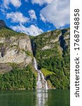 A waterfall hits from a crevice from the steep cliffs of the Geiranger Fjord, Norway. - stock photo