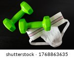 Small photo of A vintage style jockstrap and two dumbbells.