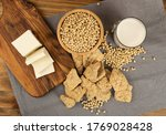 Soy foods collection with dry soy meat, soybeans, milk and tofu on wood rustic background top view. Soy products mix with bean curd, soy protein or TSP