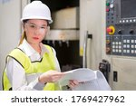 Small photo of Female engineer is checking program and parameter of CNC machine.