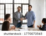 Small photo of Boss shake hands introduces new employee to members during briefing in board room, staff clap hands encourage newcomer welcoming express regard. Praise and appreciation, best worker of month concept