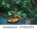 Small photo of Girl relaxing and eating floating breakfast in jungle pool on luxury villa in Bali. Valentines day or honeymoon surprise. Tropical travel lifestyle. Black rattan tray in heart shape.