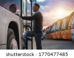 Caucasian Male Passenger in His 40s Getting Into Public Shuttle Bus on the Bus Station. Many Coaches Parked in Background. - stock photo
