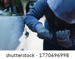 image of thief trying to break into a car. - stock photo