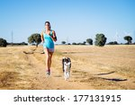 Stock photo woman and dog running in country side dirt track female runner exercising and training with her 177131915