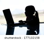 A silhouette of a young girl on the computer may be in danger due to a cyberbully or internet predator.  She is in the dark. - stock photo
