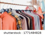 Small photo of Variety and modern fashion clothes, orderly hanging on the clothesline. Clothes hang on shelf in a designer clothes store. Row of clothes hanging on rack. Fashion trend concept.
