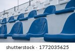 Empty grandstand with blue and white seats outdoors.
