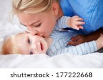 Mother Kissing Baby Son As The...
